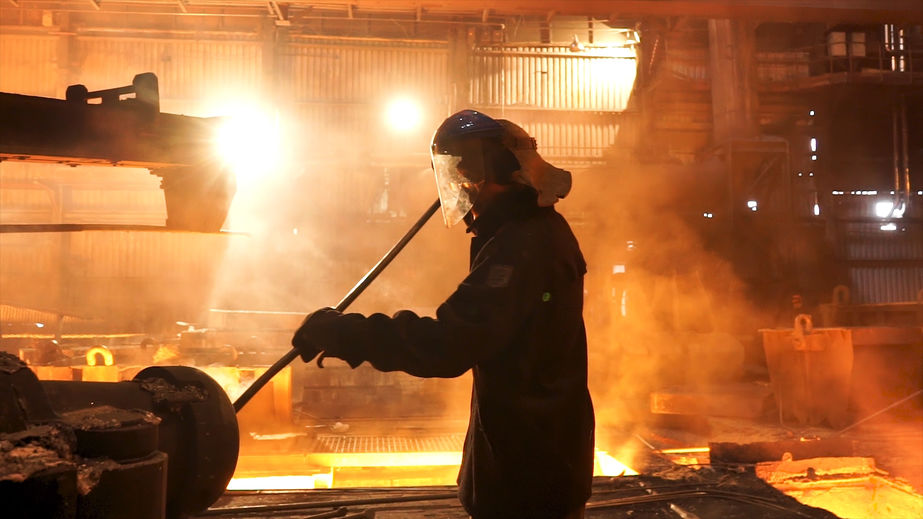 Side view of the perator remove waste from furnace pipe at the iron melting plant. Stock footage. Man worker in heat resistant suit cleaning high temperature furnace.
